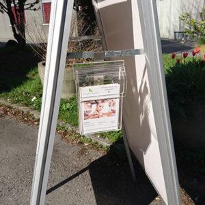 Acryl Prospektbox mit Deckel angehängt an einem Kundenstopper mit Prospekten drin