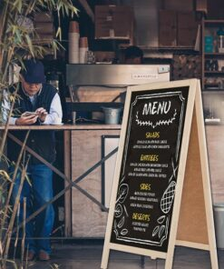 Kundenstopper aus Holz in der Farbe natur, mit schwarzer Kreidetafel, positioniert im Restaurant