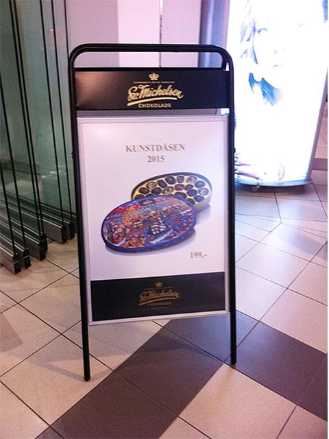 Kundenstopper aus Stahl mit Topschild für das Logo, schwarz, Andwendungsbeispiel in einem Ladengeschäft
