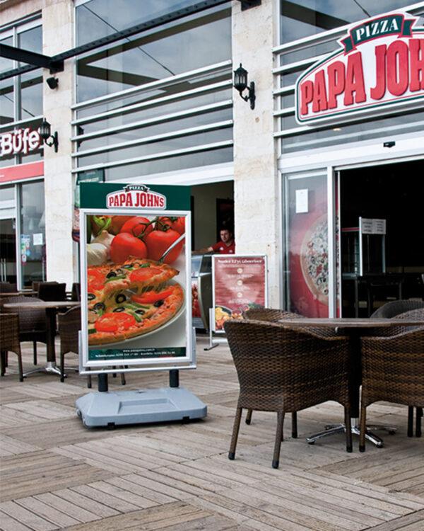 Massiver und windfester Strassenständer platziert in einem Restaurant im Aussenbereich mit Plakaten am POS