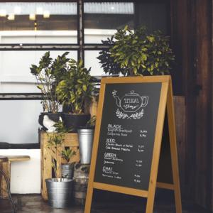 Holz Kundenstopper Hellbraun beschriftet mit weissen Securit Kreidemarker und aufgestellt vor einem Teeladen