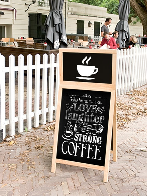 Kundenstopper aus Holz mit Logoschild, platziert vor einem Kaffee