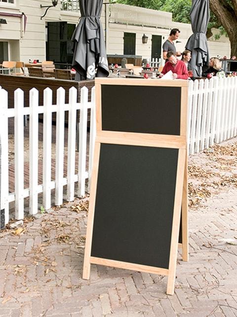 wetterfester holz kundenstopper mit topschild aufgestellt auf dem bürgersteig, schwarze tafeln für beschriftung mit kreide oder kreidemarker