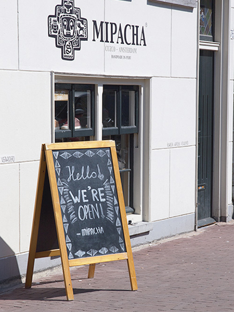 wetterfester holz kundenstopper in hellbraun, schwarze kreidetafel zum beschriften, produkt ist aufgestellt am point of sale