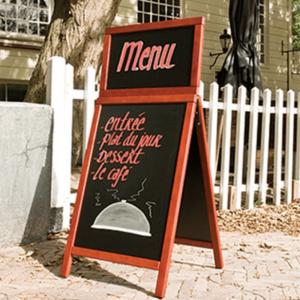aufgestellter Holz Kundenstopper mit Kreidetafel beschriftet vor einem Restaurant im Aussenbereich
