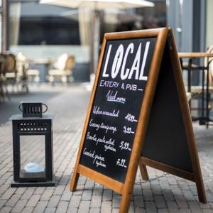 Holzafusteller mit Kreidetafel beschriftet mit Kreidemarker und aufgestellt vor einem Pub mit dem Tagesangebot