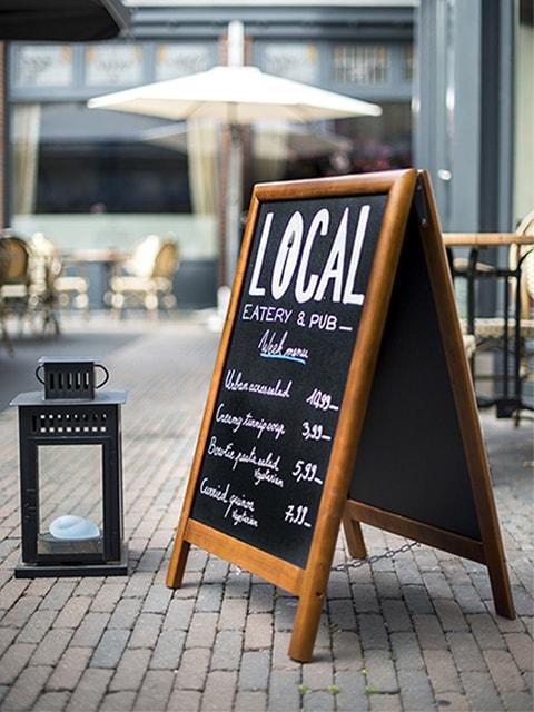 wetterfester holzaufsteller positioniert vor einem restaurant im aussenbereich, kreideoberfläche beschriftet mit kreidemarker, holurahmen dunkelbraun