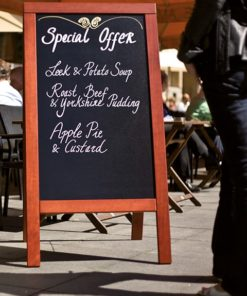 wetterfester holz kundenstopper mit beschrifteter kreidetafel, positioniert vor einem restaurant, kunde schaut sich den holzaufsteller an
