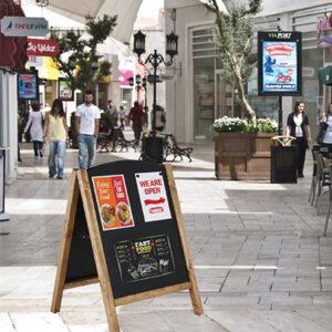 stabiler Holzaufsteller A Aufsteller mit magnetischer Kreidetafel aufgestellt auf einer Einkaufspassage